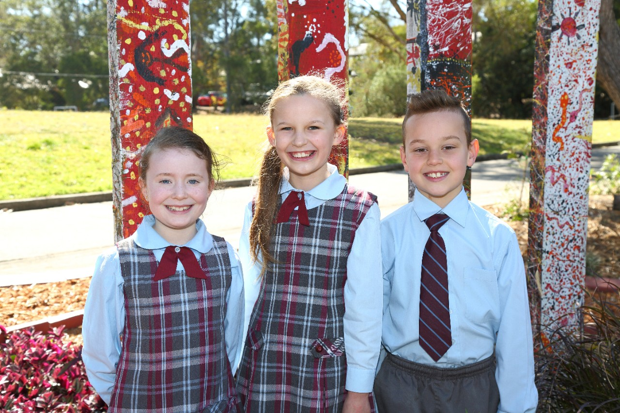 Three students stand in front of the Bulwannada Garden at Mount St Thomas Public School.